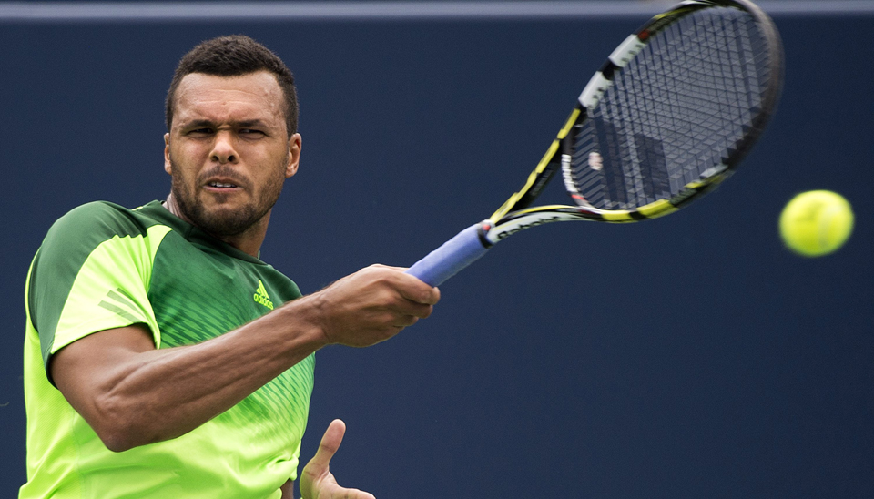 Jo-Wilfried Tsonga, of France, returns the ball against Novak Djokovic, of Serbia, in a men's third round match at the Rogers Cup.