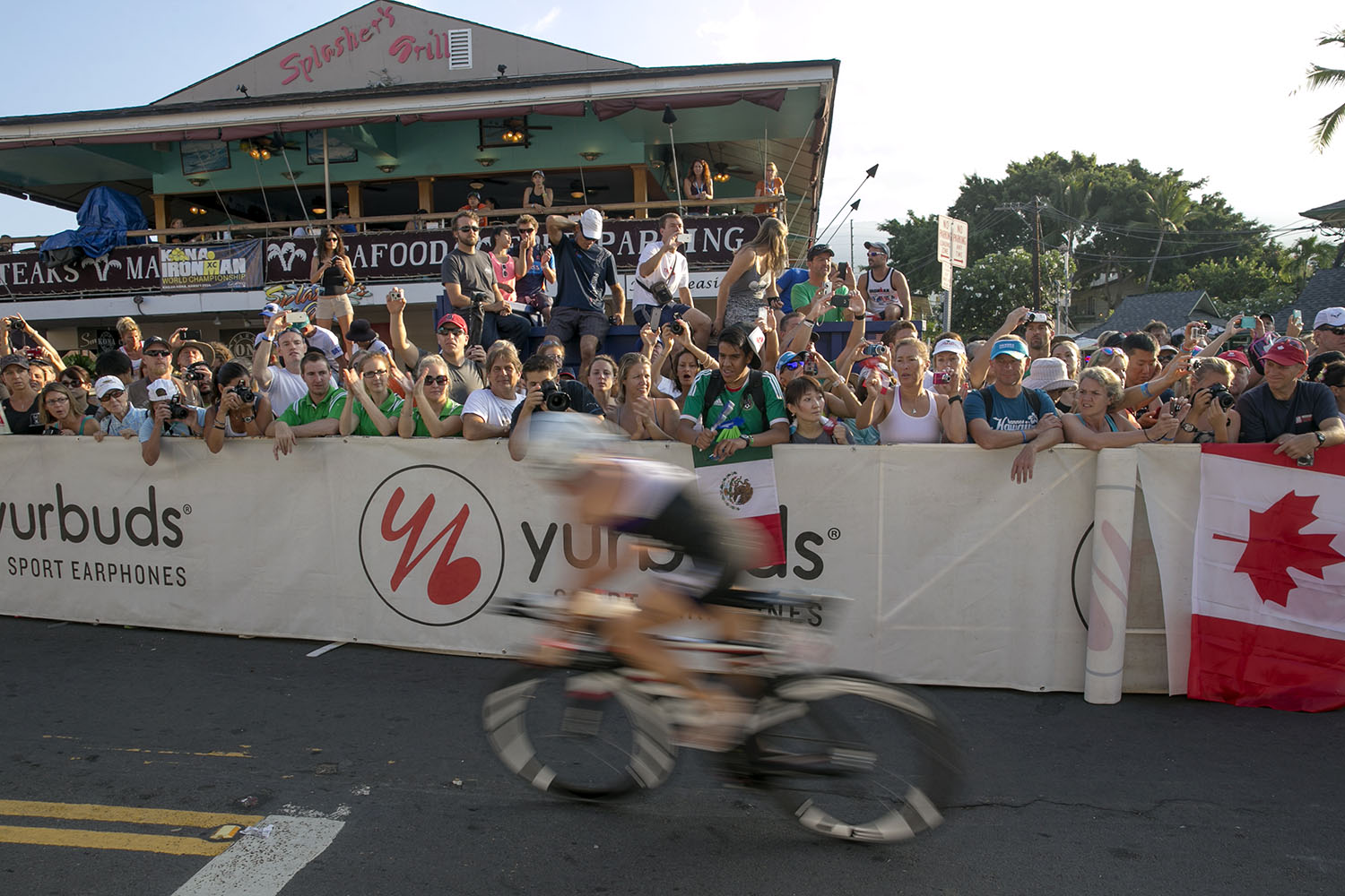 Onlookers watch bicyclist at the start of the 112-mile bike race of the 2014 IRONMAN World Championship.