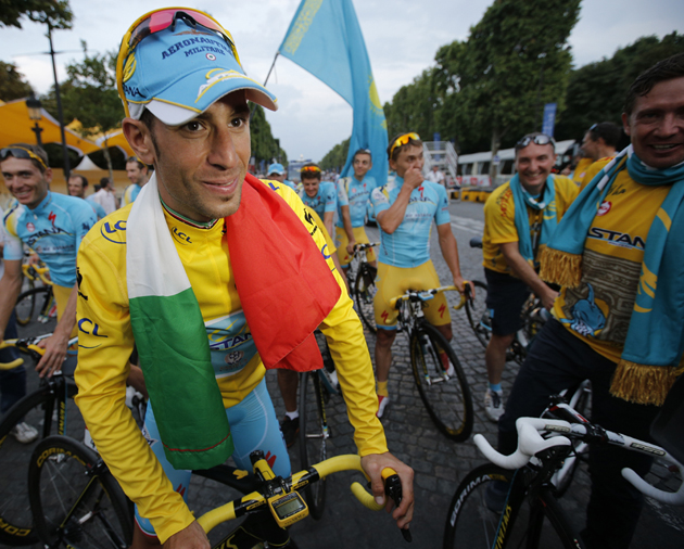 2014 Tour de France cycling race winner Italy's Vincenzo Nibali wears the Italian flag as he is about to ride in the team parade of the Tour de France.
