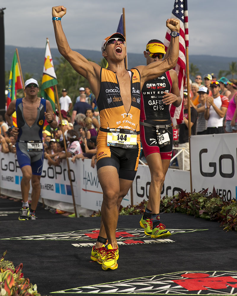 Former Olympian Apollo Ohno crosses the finish line at the 2014 IRONMAN World Championship.