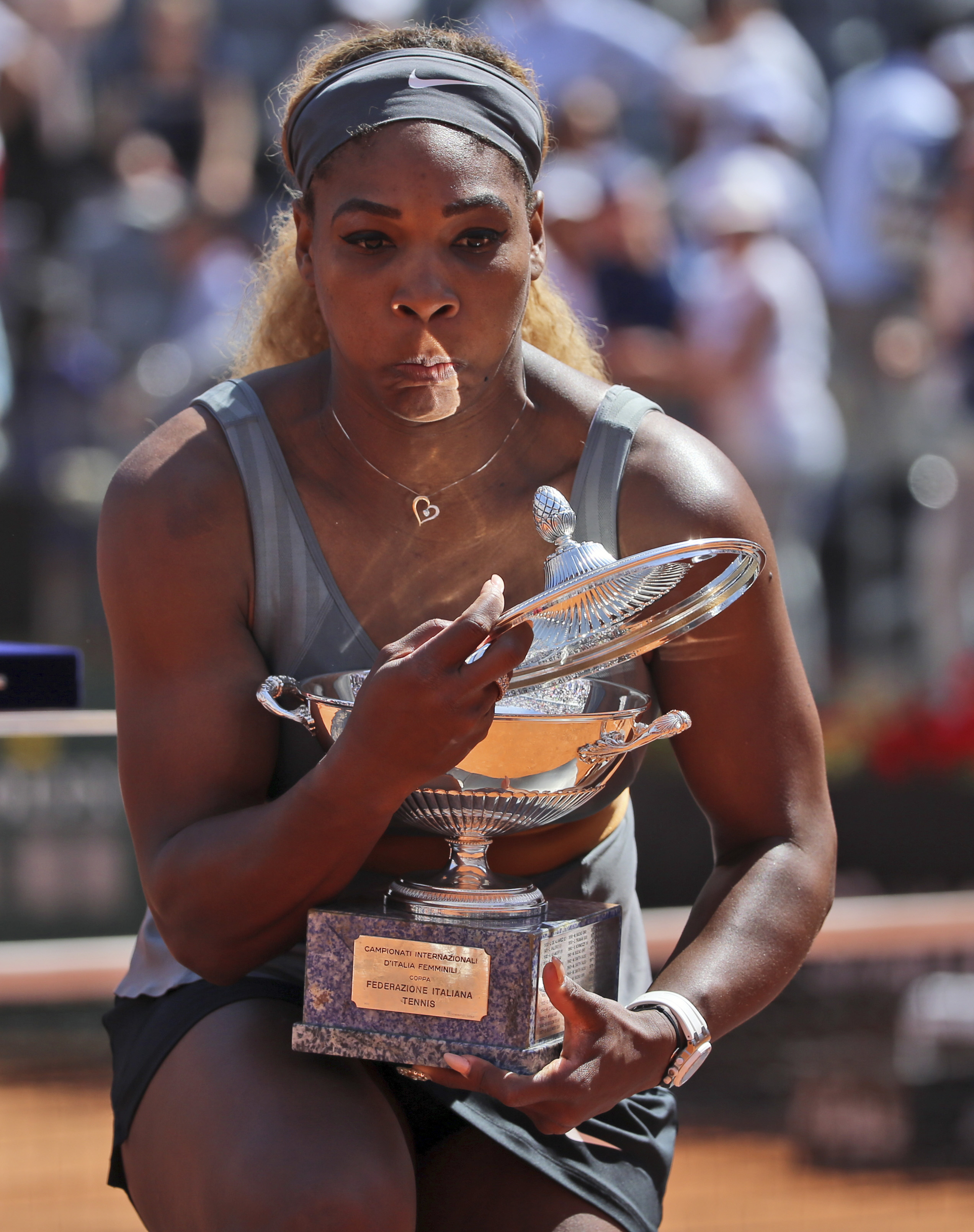 Serena fumbles with her trophy at the Italian Open.