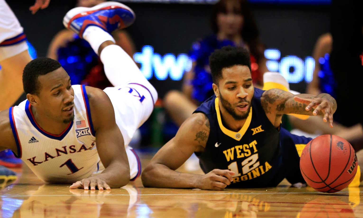 West Virginia guard Tarik Phillip and Kansas guard Wayne Selden Jr. scramble for a loose ball.