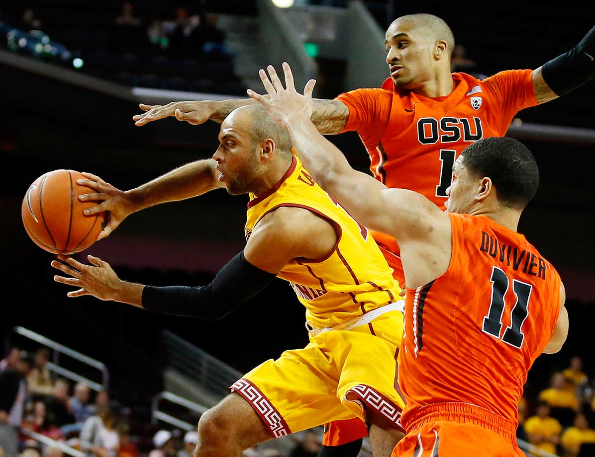 Southern California's Julian Jacobs passes as he jumps between Oregon State's Gary Payton II and Malcolm Duvivier.