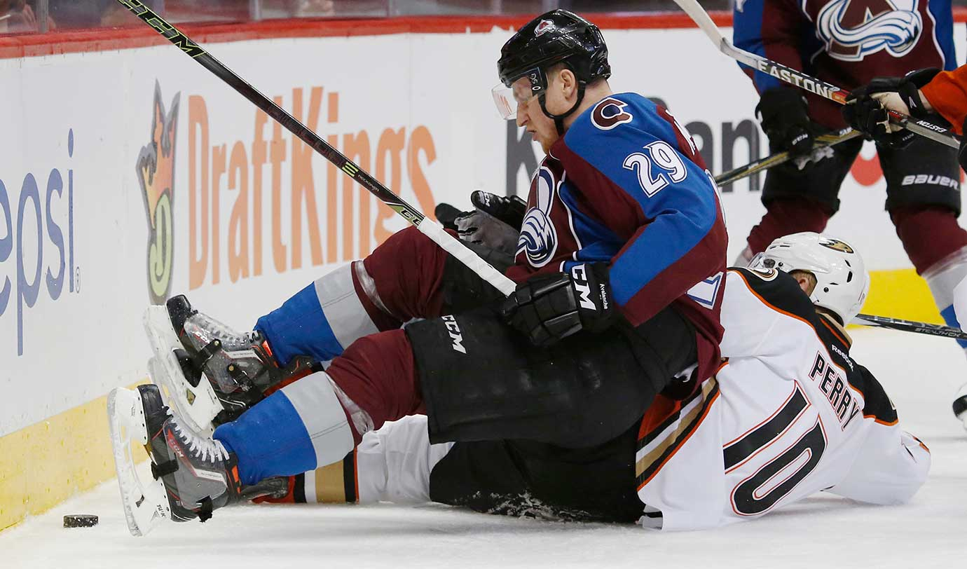 Colorado Avalanche center Nathan MacKinnon lands on top of Anaheim's Corey Perry while pursuing the puck.