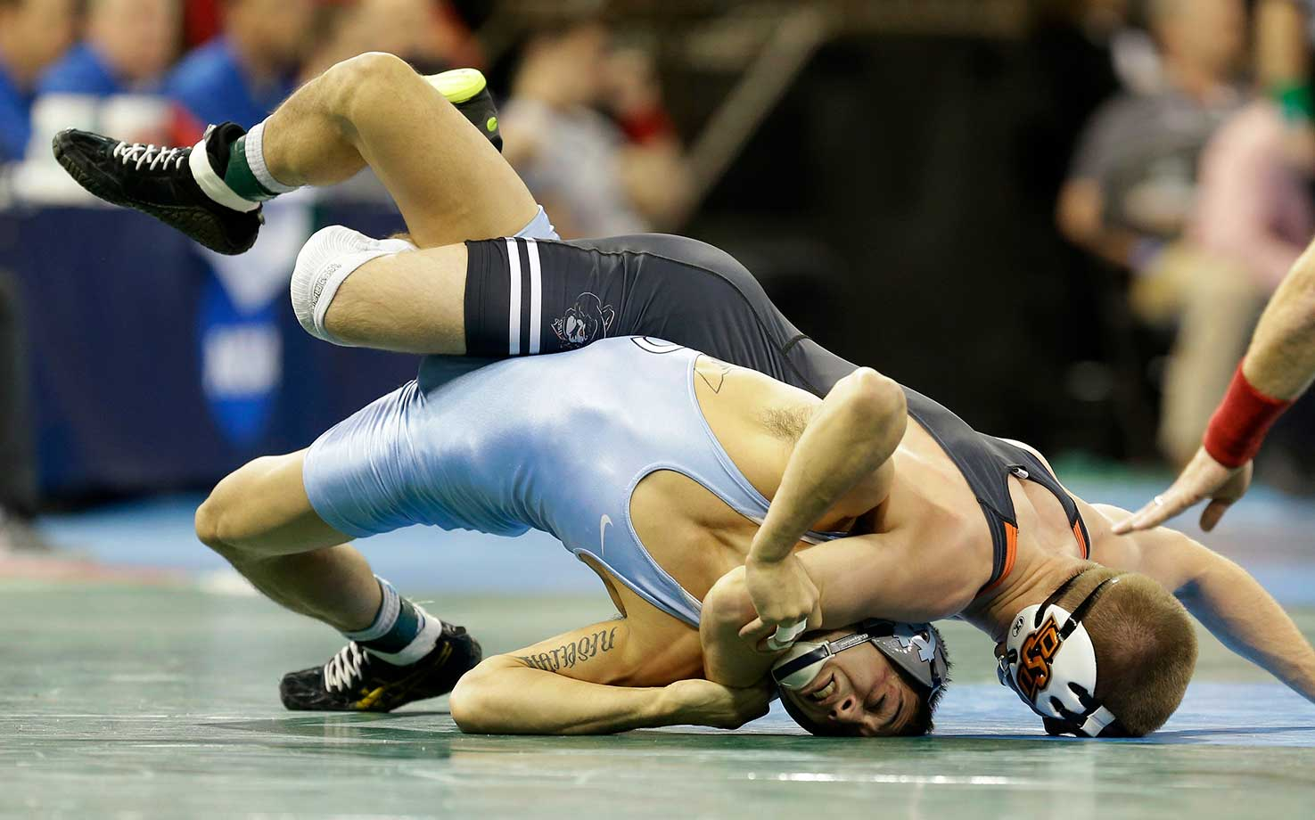 North Carolina's Joseph Ward, left, gets tangles up with Oklahoma State's Dean Heil in a 141-pound match during the NCAA Division 1 wrestling championship.