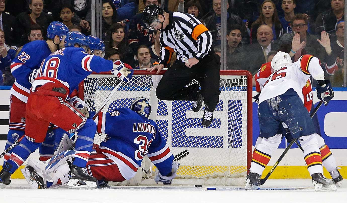 Referee T.J. Luxmore jumps to avoid the puck as New York Rangers goalie Henrik Lundqvist lunges for a save.