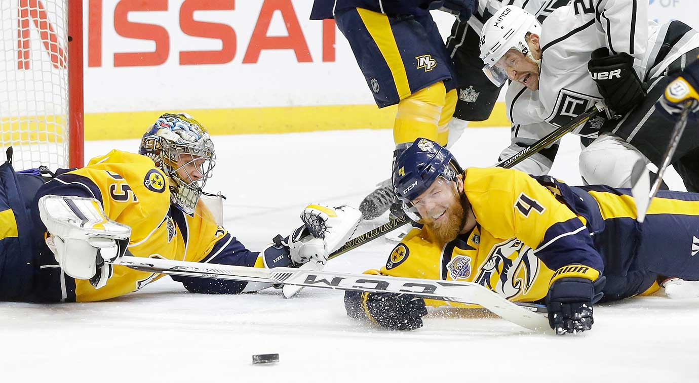 Nashville goalie Pekka Rinne, defenseman Ryan Ellis and L.A. Kings center Trevor Lewis dive for the puck.