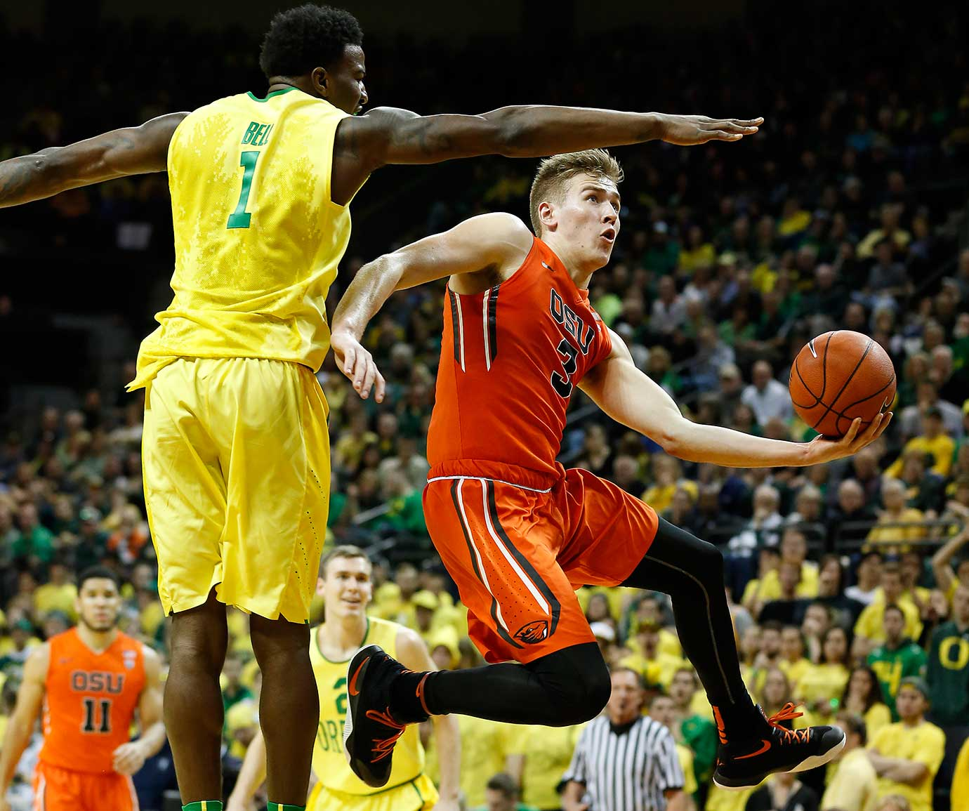 Oregon State's Tres Tinkle jumps toward the basket in front of Oregon's Jordan Bell.