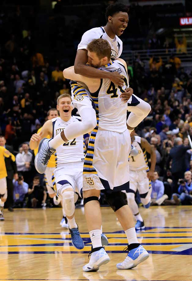 Marquette's Luke Fischer is swarmed after making free throws in the final seconds of an 88-87 win over Georgetown.