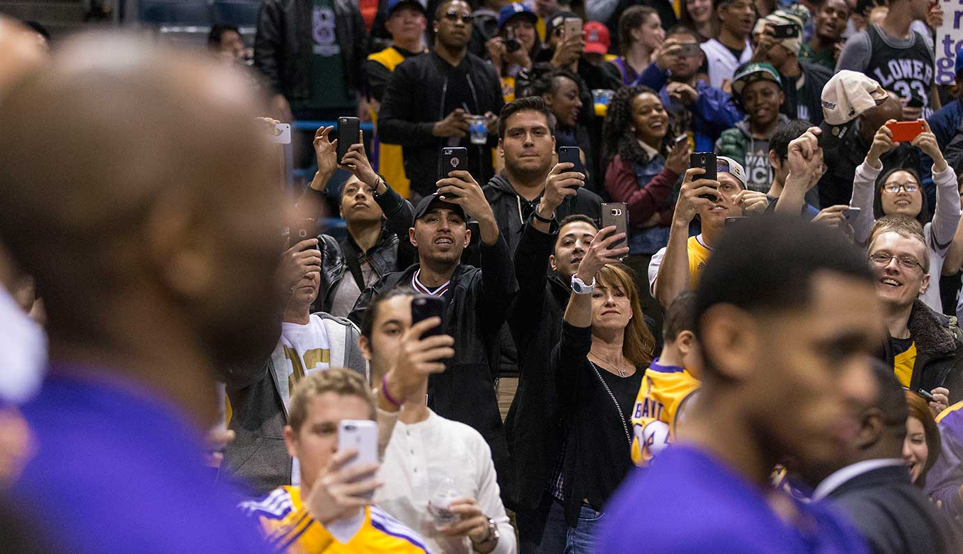 Fans of the retiring Kobe Bryant try to get a photo of him as the game with the Bucks comes to an end in his last visit to Milwaukee as a player.