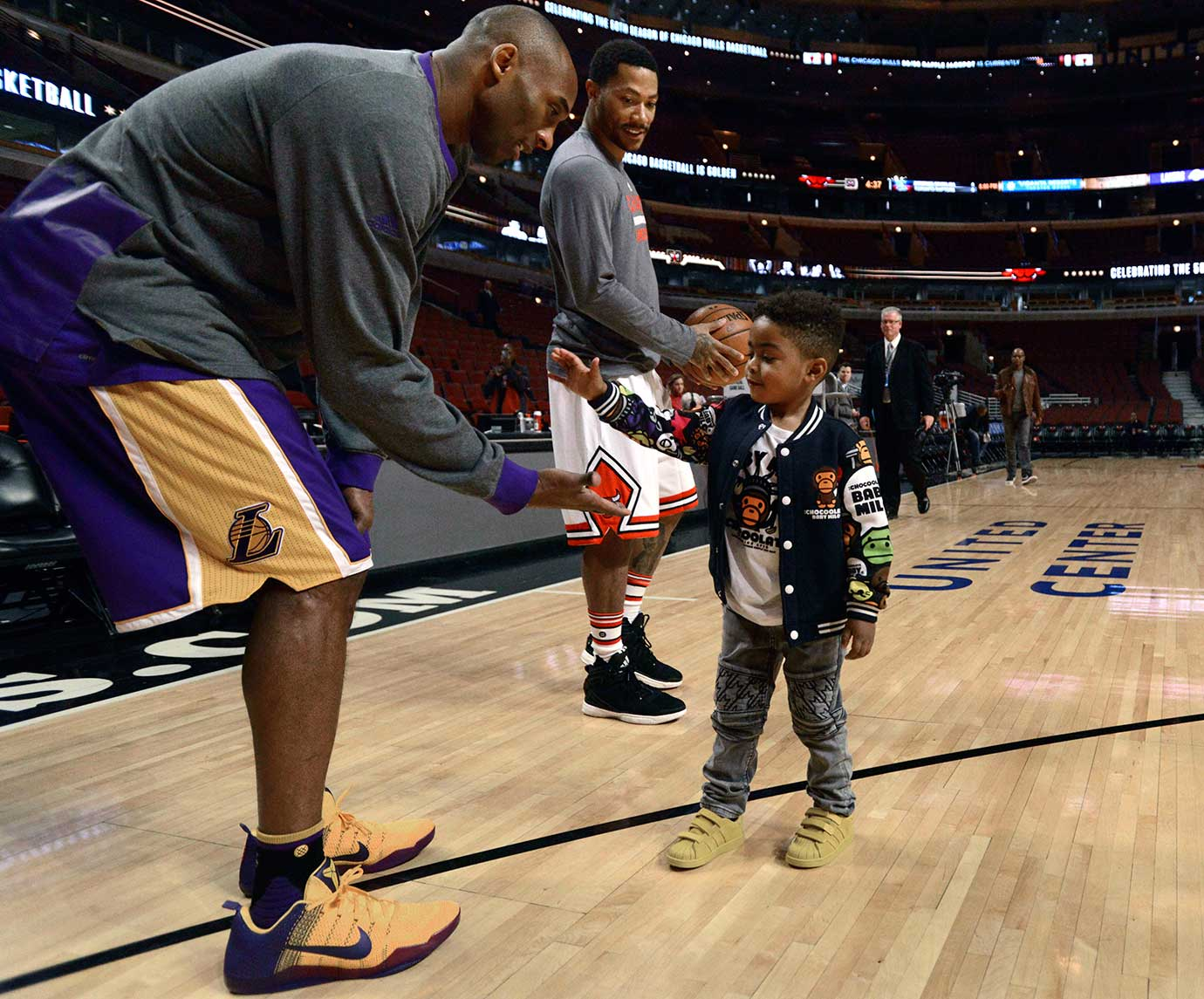 Kobe Bryant greets P.J. Rose while Derrick Rose warms up up before a Lakers-Bulls game in Chicago.