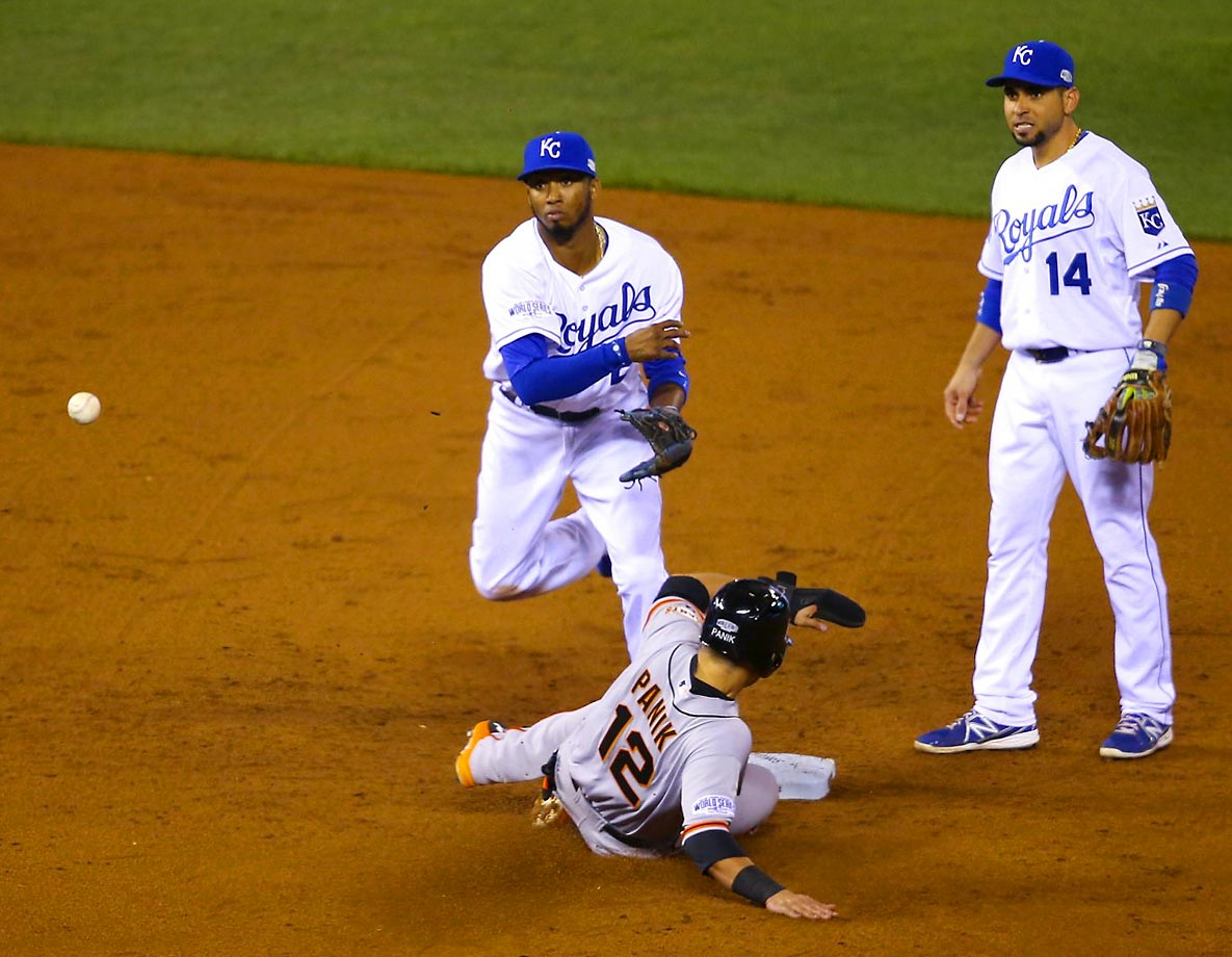Shortstop Alcides Escobar turns a double play against Joe Panik of the Giants.