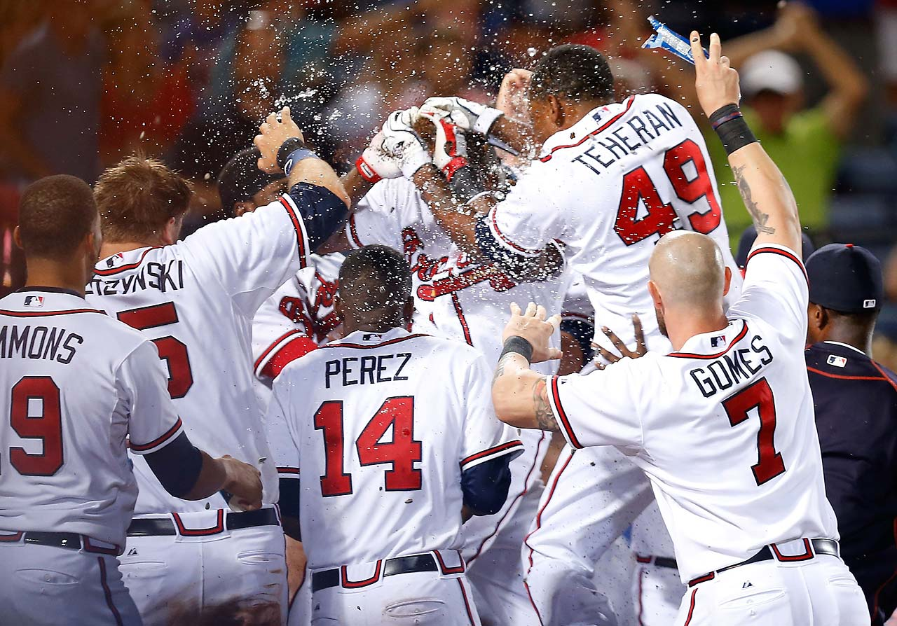 Adonis Garcia (24) is mobbed by teammates after hitting a game winning, two-run home run in the 12th inning against the San Francisco Giants at Turner Field.