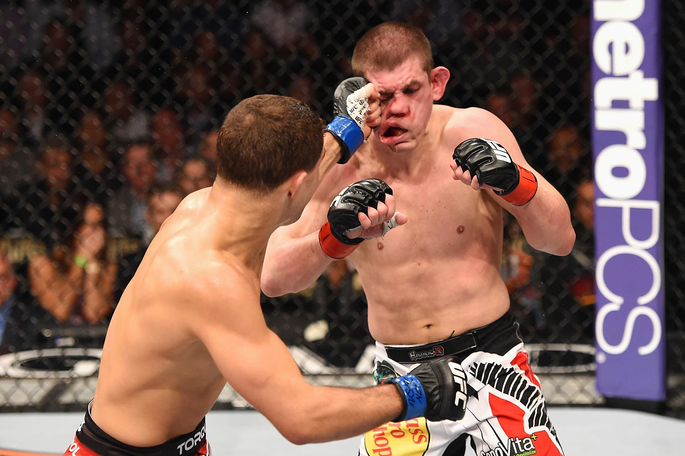 Al Iaquinta punches Joe Lauzon in their lightweight bout at the UFC 183 event in Las Vegas.