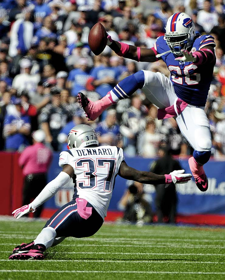 Buffalo Bills running back Anthony Dixon hurdles New England Patriots cornerback Alfonzo Dennard.