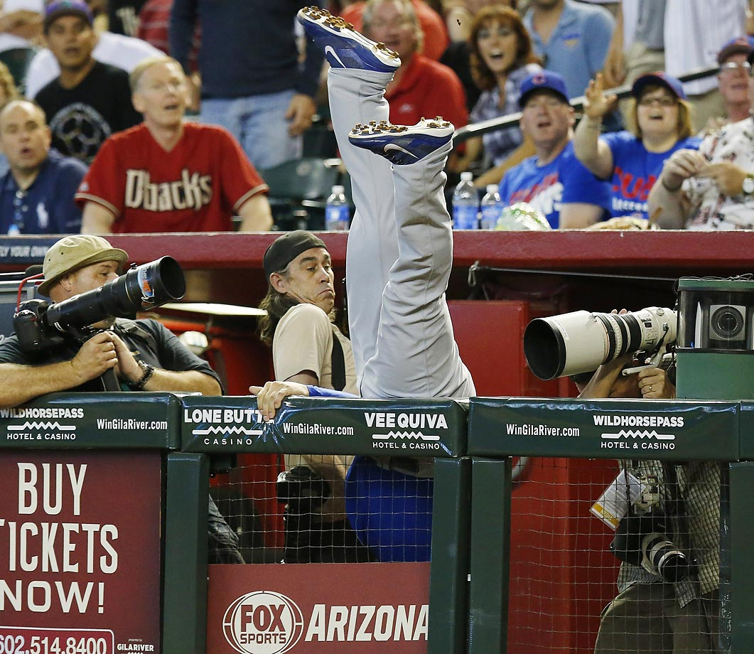 Photographers dodge a diving Anthony Rizzo as he catches a foul out off the bat of Arizona Diamondbacks' Aaron Hill at Chase Field in Phoenix.