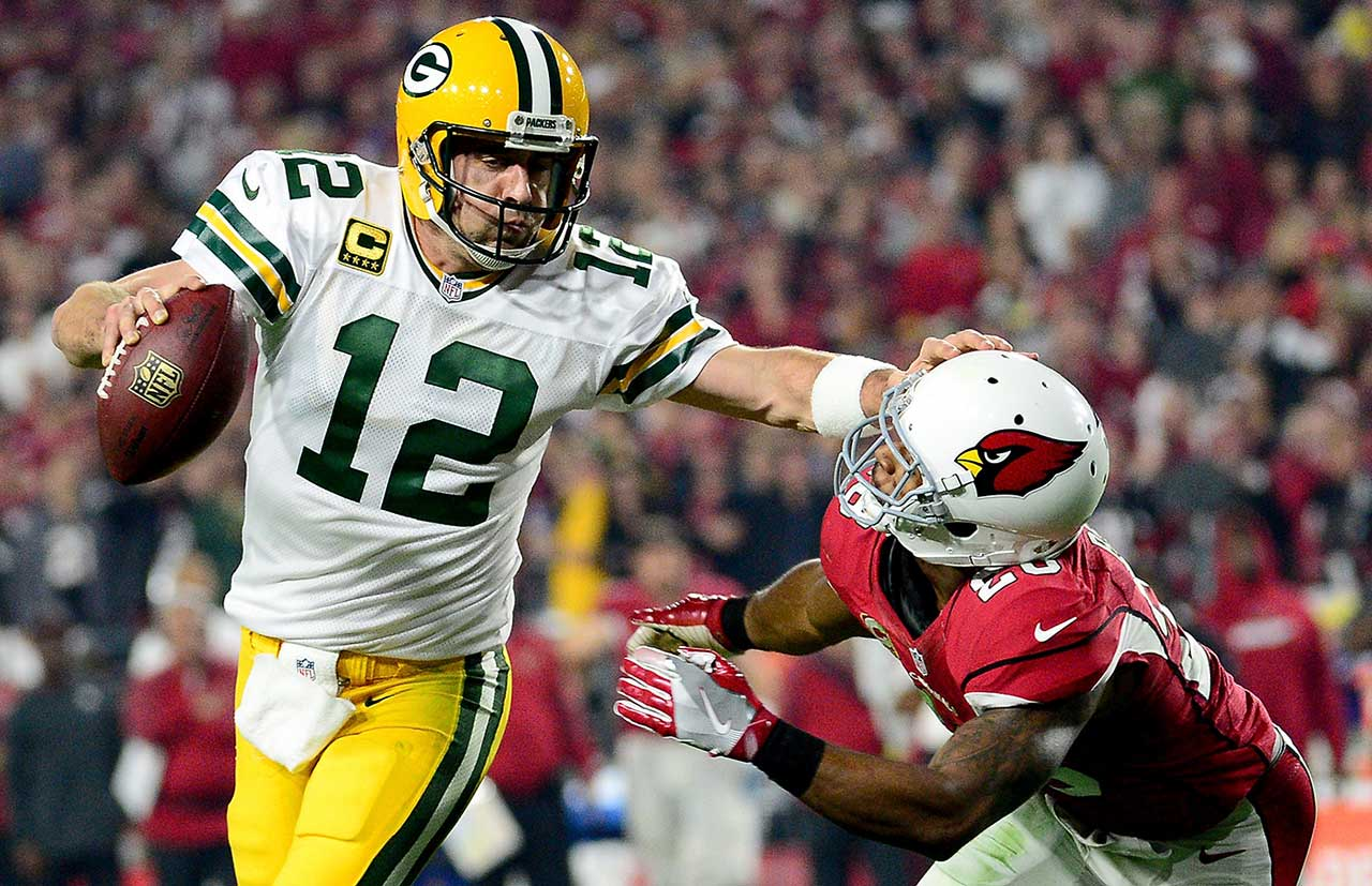 Aaron Rodgers  is hit by cornerback Justin Bethel.
