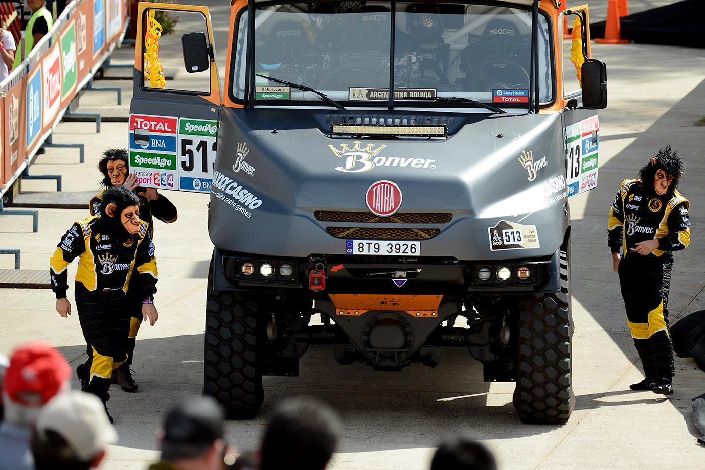 Competitors from the Bonver Dakar project team arrive at the podium wearing monkey masks during the symbolic start of the 2016 Dakar Rally.