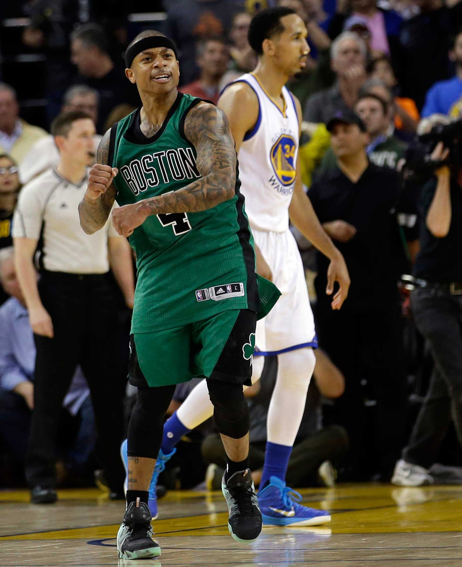 Isaiah Thomas of Boston celebrates and Shaun Livingston of Golden State walks off the court at the end of the Celtics' 109-106 win over the Warriors. Their previous game went to double overtime.