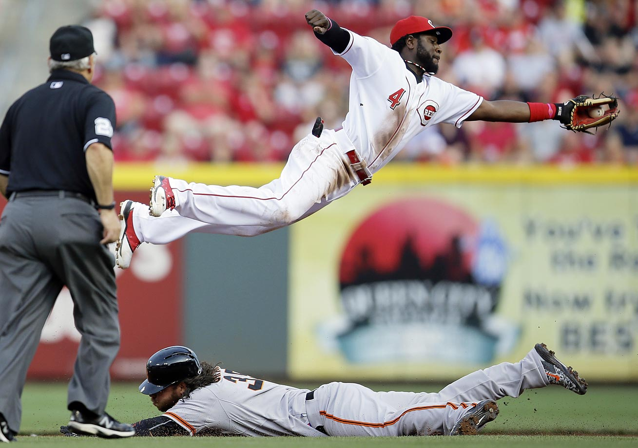 Brandon Crawford of the San Francisco Giants steals second base under Brandon Phillips of the Cincinnati Reds.