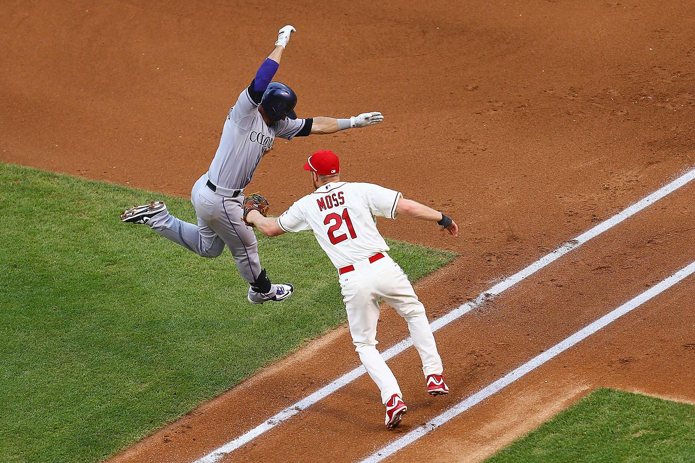 Brandon Moss of the St. Louis Cardinals tags out Daniel Descalso of the Colorado Rockies at Busch Stadium.