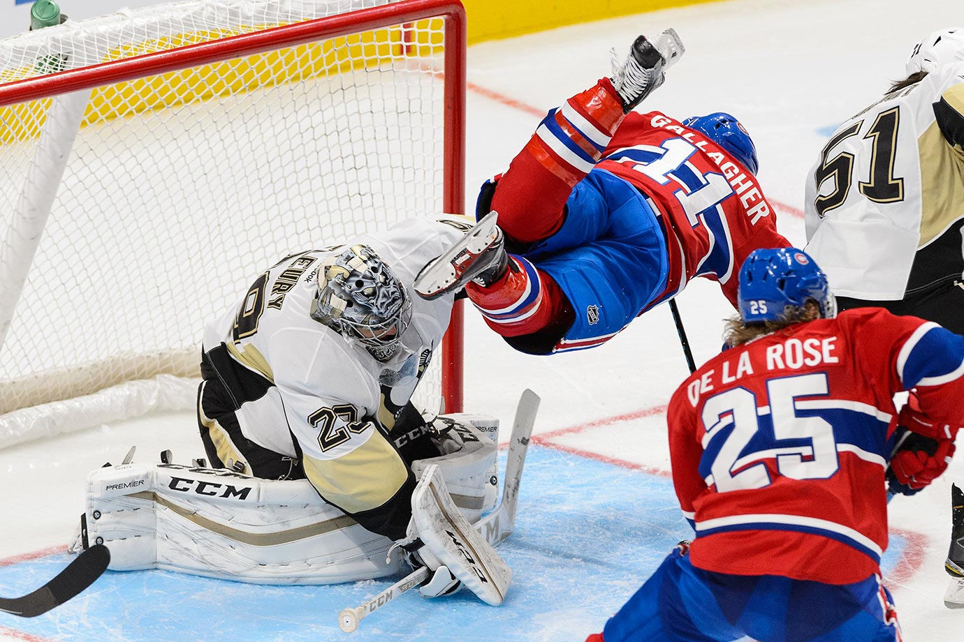 Brendan Gallagher of the Montreal Canadiens takes flight over goaltender Marc-Andre Fleury of Pittsburgh.