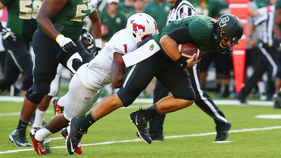 Taylor Yenga (left) drives his facemask into the back of Baylor QB Bryce Petty during the Bears' 45-0 win in Waco Sunday night.