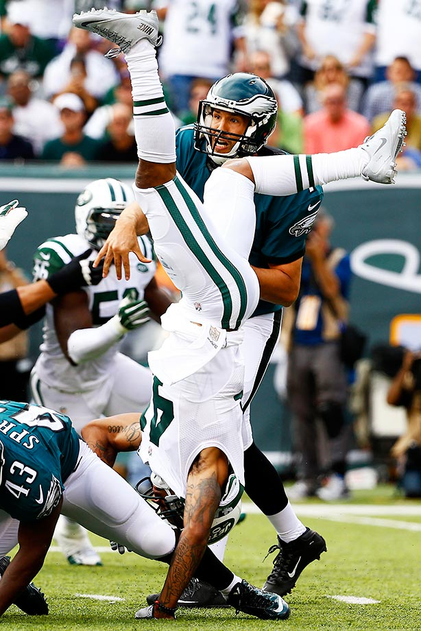 Buster Skrine flips upside down as he defends against  Sam Bradford.