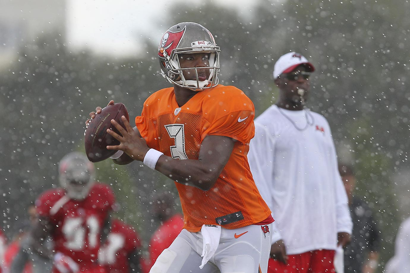 Tampa Bay quarterback Jameis Winston drops back to pass in the pouring rain during a Buccaneers training camp workout in Tampa.