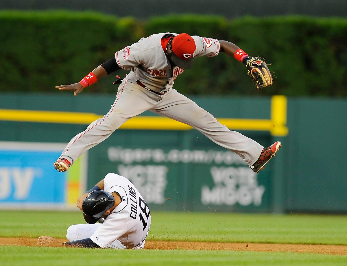 Brandon Phillips of the Cincinnati Reds leaps over Tyler Collins of the Detroit Tigers after throwing to first for a double play.