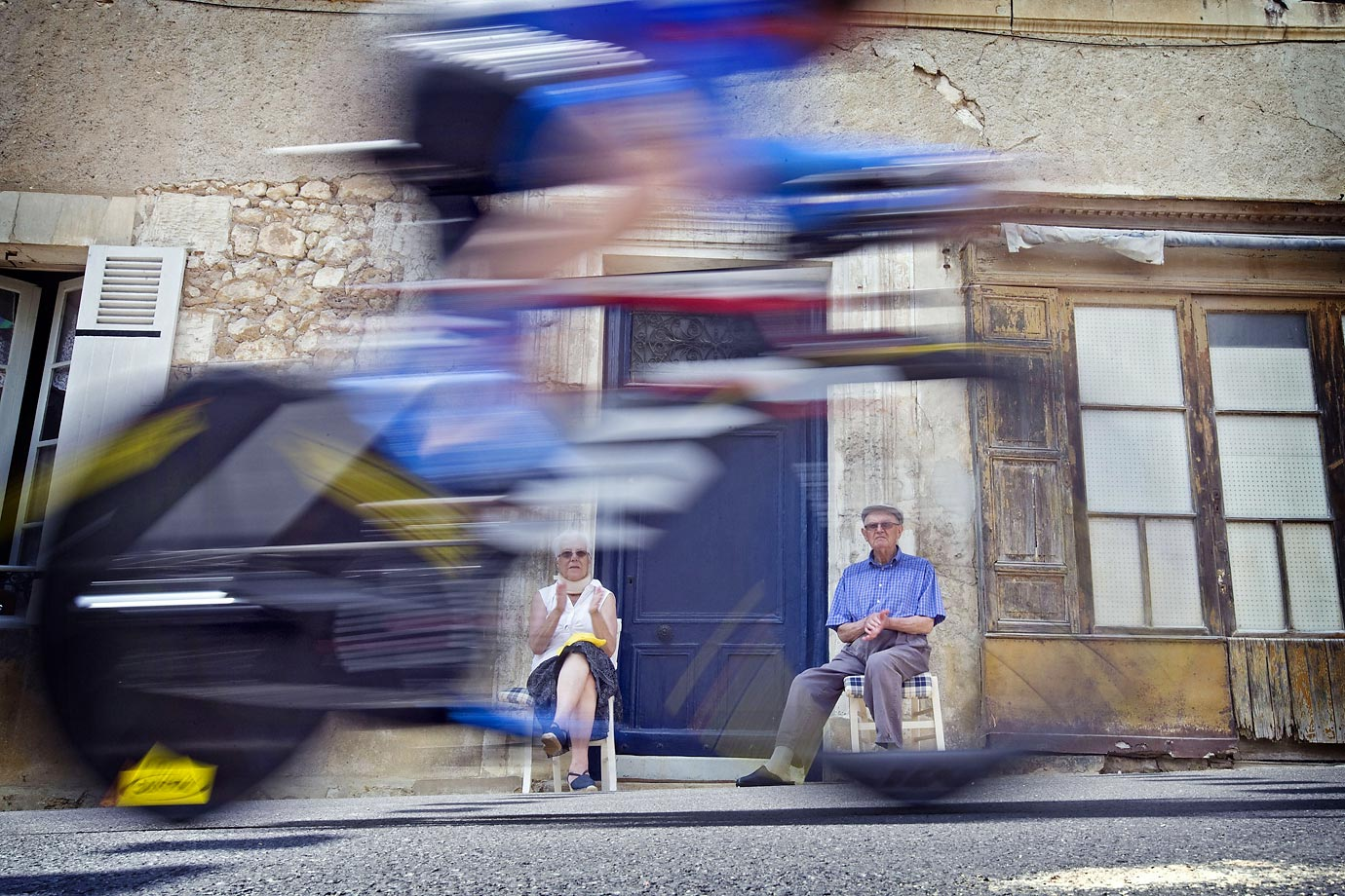 Spectators look on as a Tour de France biker zooms past.