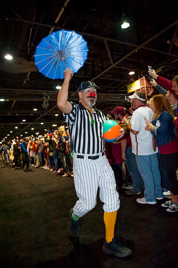 A clown referee leads the team parade through the fans before the 2015 Chick-Fil-A Peach Bowl.