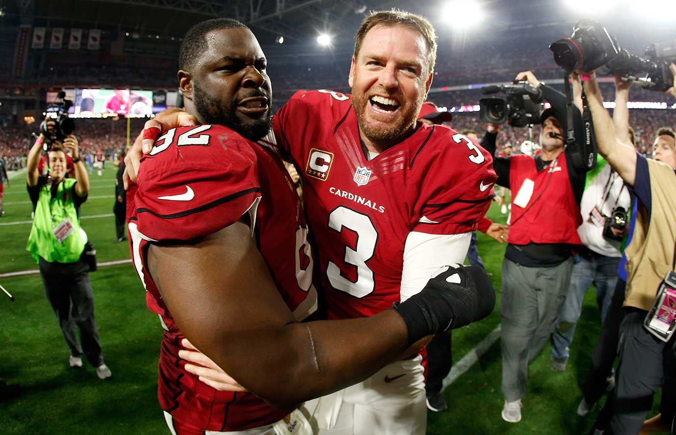 Carson Palmer and defensive end Frostee Rucker walk off the field victorious after an overtime win sent them to a NFC Championship Game matchup against the Carolina Panthers. Palmer pulled off a five-yard shovel pass to Larry Fitzgerald for the decisive touchdown in overtime.