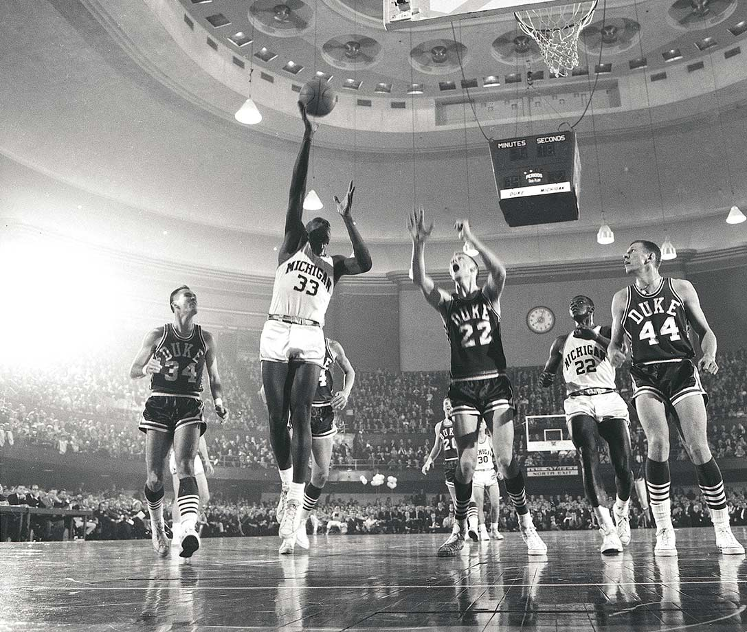 "Michigan's Crisler Arena, which opened in 1967, is also known as ""The House that Cazzie Built"" despite the fact that Russell never played a game there. Russell scored 30 points and grabbed 14 rebounds in his first varsity game for the Wolverines, a feat that would become merely average by his senior year, in which he averaged 30.8 points. Michigan's all-time leader in scoring, Russell set a new record for points in a season each year, progressively breaking his own record by setting the bar a little bit higher. The Wolverines reached the 1964 Final Four his sophomore year and got a game further the next year before falling to UCLA. Although Michigan lost to Kentucky in the Elite Eight in Russell's final season, he won the Helms Foundation Player of the Year in addition to his second Big Ten MVP Award."
