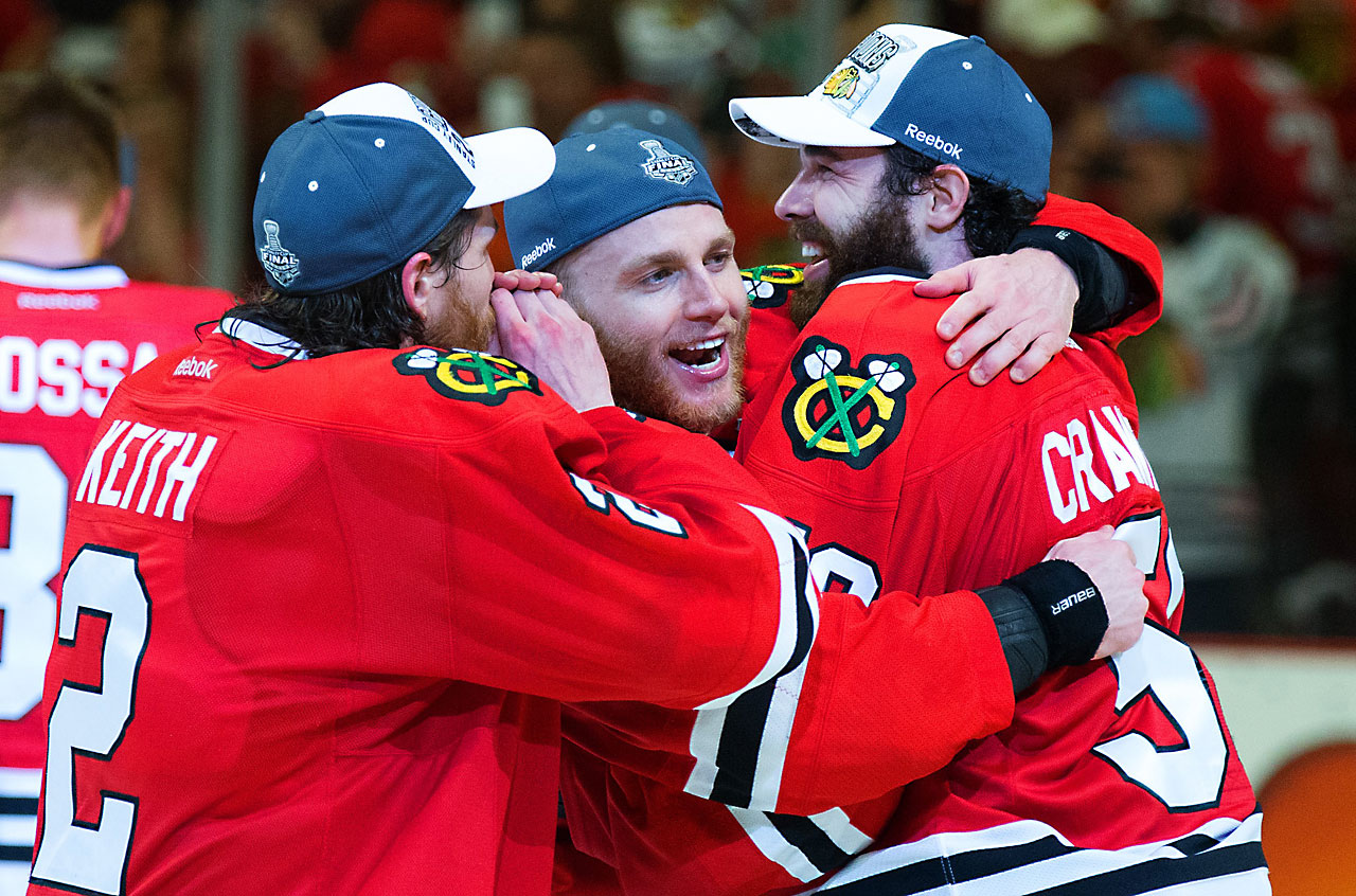 Duncan Keith (2), Patrick Kane and Corey Crawford enjoy an embrace during the postgame celebration.
