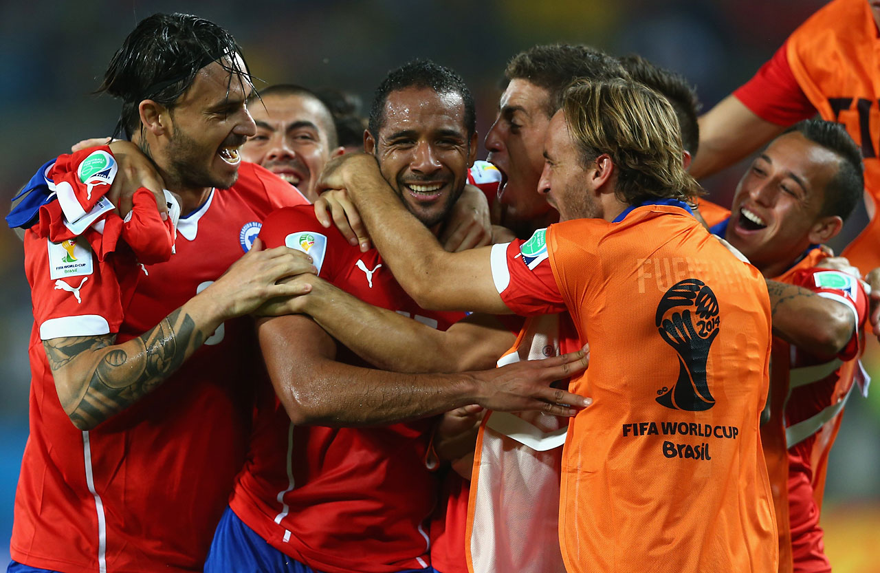 Jean Beausejour of Chile is congratulated by teammates after scoring his team's third goal against Australia at Arena Pantanal on June 13.