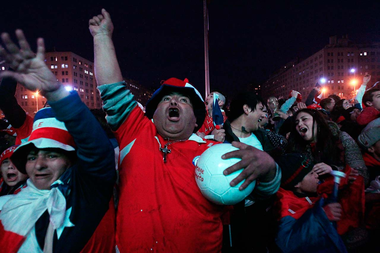 Soccer fans cheer as they watch Chile's Jorge Valdivia score the second goal of the World Cup match between Chile and Australia, via a live broadcast on a giant screen in front of La Moneda presidential palace, in Santiago, Chile.  Chile went on to defeat Australia 3-1 in the group B game at the Arena Pantanal in Cuiaba, Brazil.