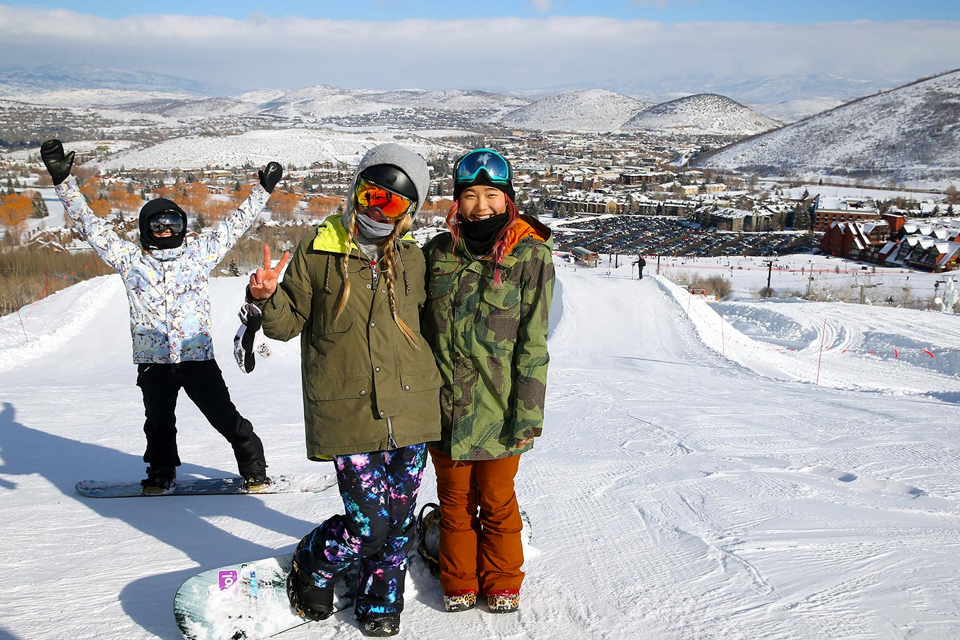 Snowboarder Chloe Kim, far right, poses for a photo with fellow snowboarder (and Olympic champion ) Hannah Teter (middle ) as three time Olympic medalist Kelly Clark (in background ) photo bombs the moment in between practice runs at Park City Resort in Park City.