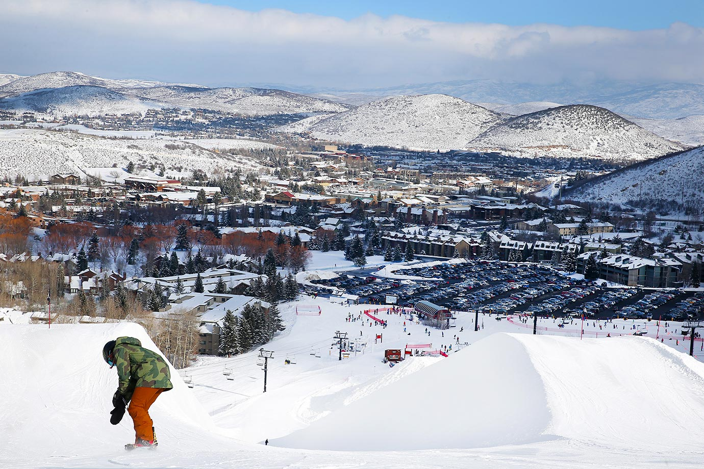 With Park City and the mountains of Utah in the background, snowboarder Chloe Kim drops down towards the half pipe at Park City.