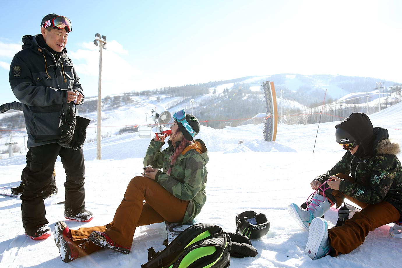 Chloe Kim grabs a snack and talks with her father Jong Jim Kim on top of the mountain.