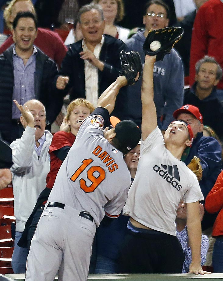 A fan beats the Orioles' Chris Davis to a foul ball during a game against the Red Sox.