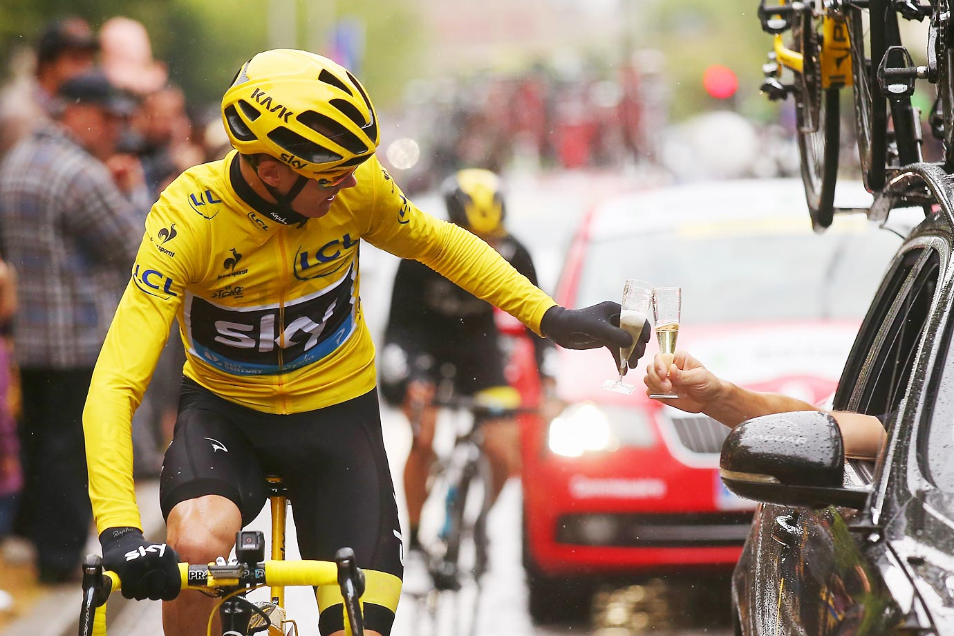 Chris Froome celebrates his Tour de France win with a glass of champagne.