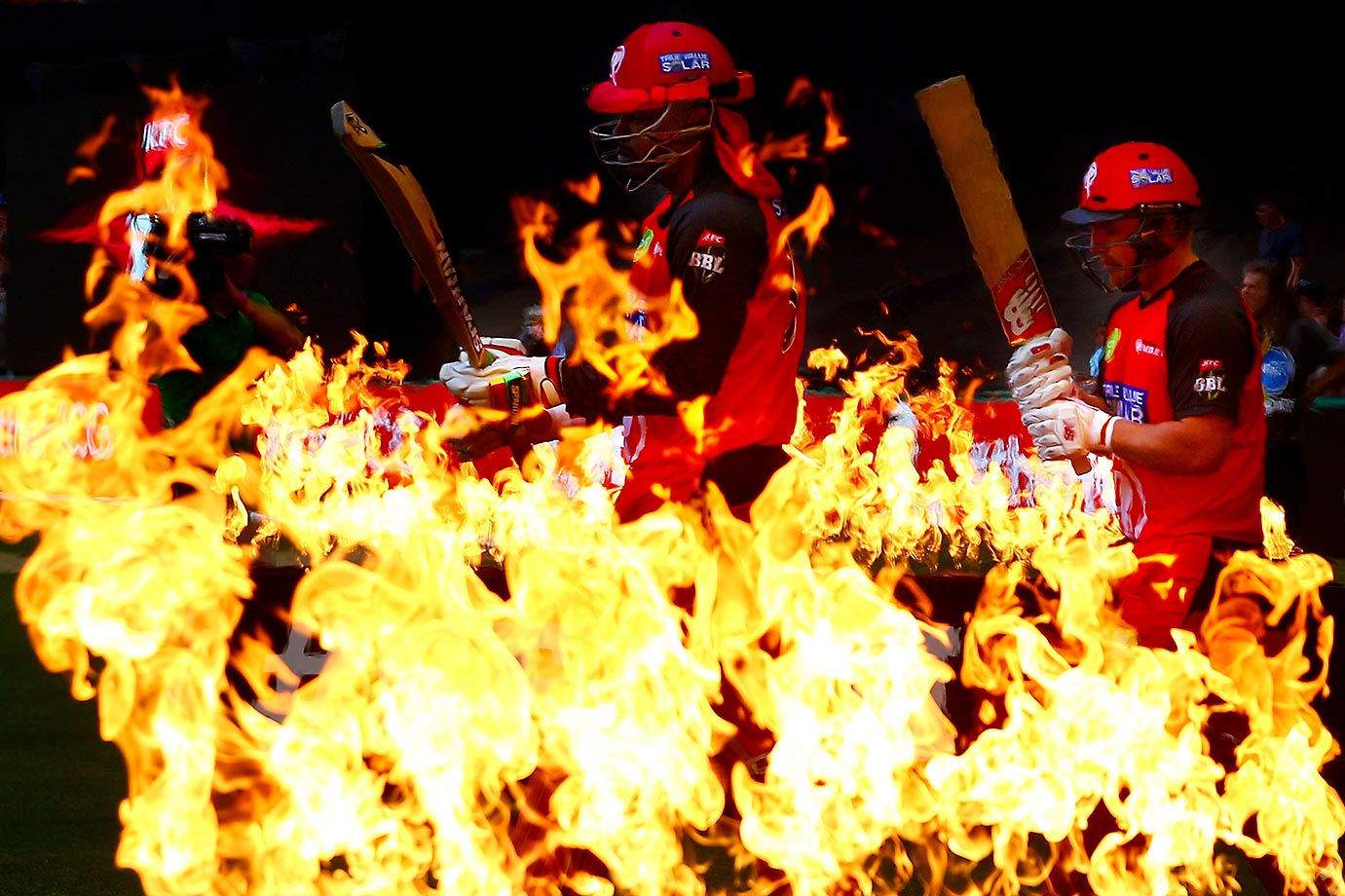 Chris Gayle and Aaron Finch of the Renegades walk through flames to open the batting during the Big Bash League match between the Melbourne Renegades and the Perth Scorchers.