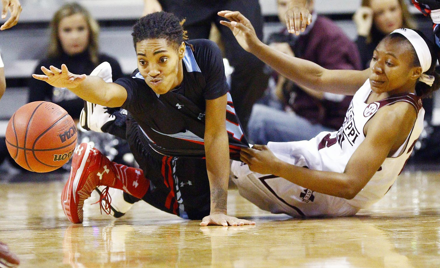 Louisiana Tech guard Chrisstasia Walter reaches for a loose ball after colliding with Mississippi State guard Morgan William.