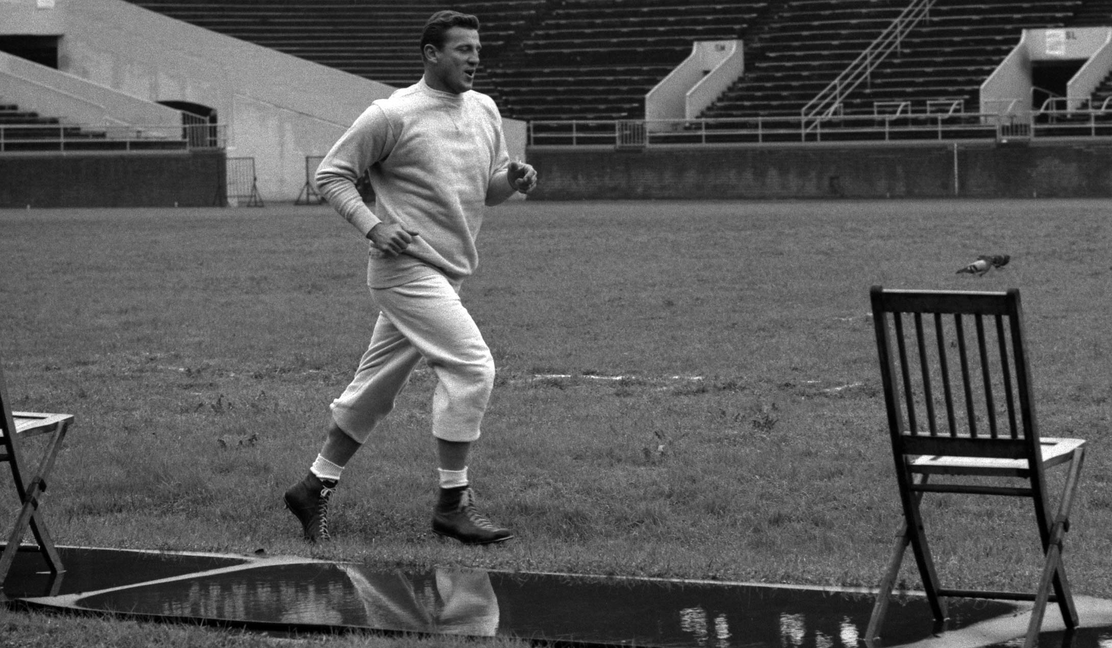 Bednarik jogs around the field prior to a practice in 1960 at Franklin Field in Philadelphia.