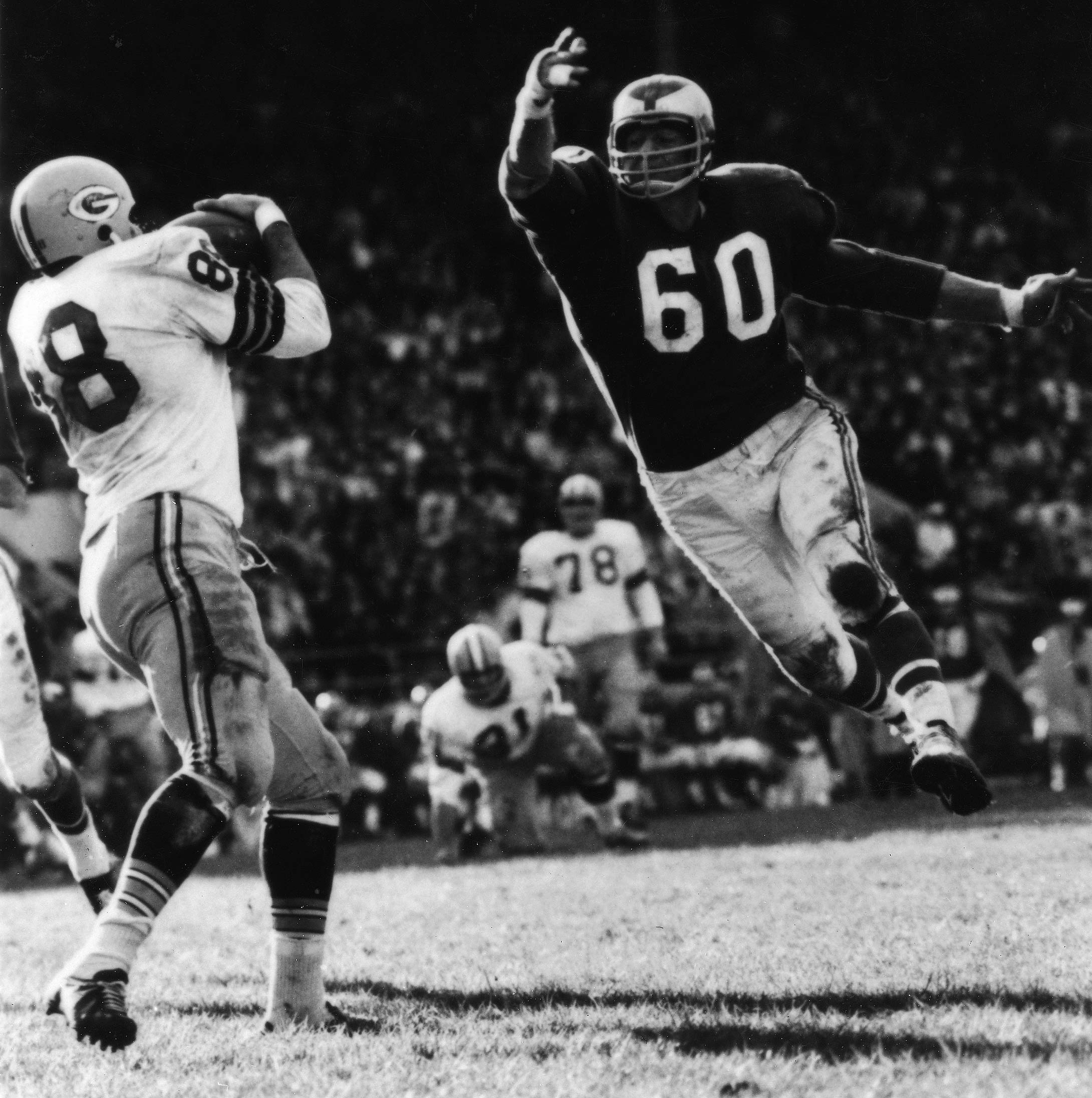 Chuck Bednarik, a two-way player for the Philadelphia Eagles, leaps toward an unidentified player from the Green Bay Packers.