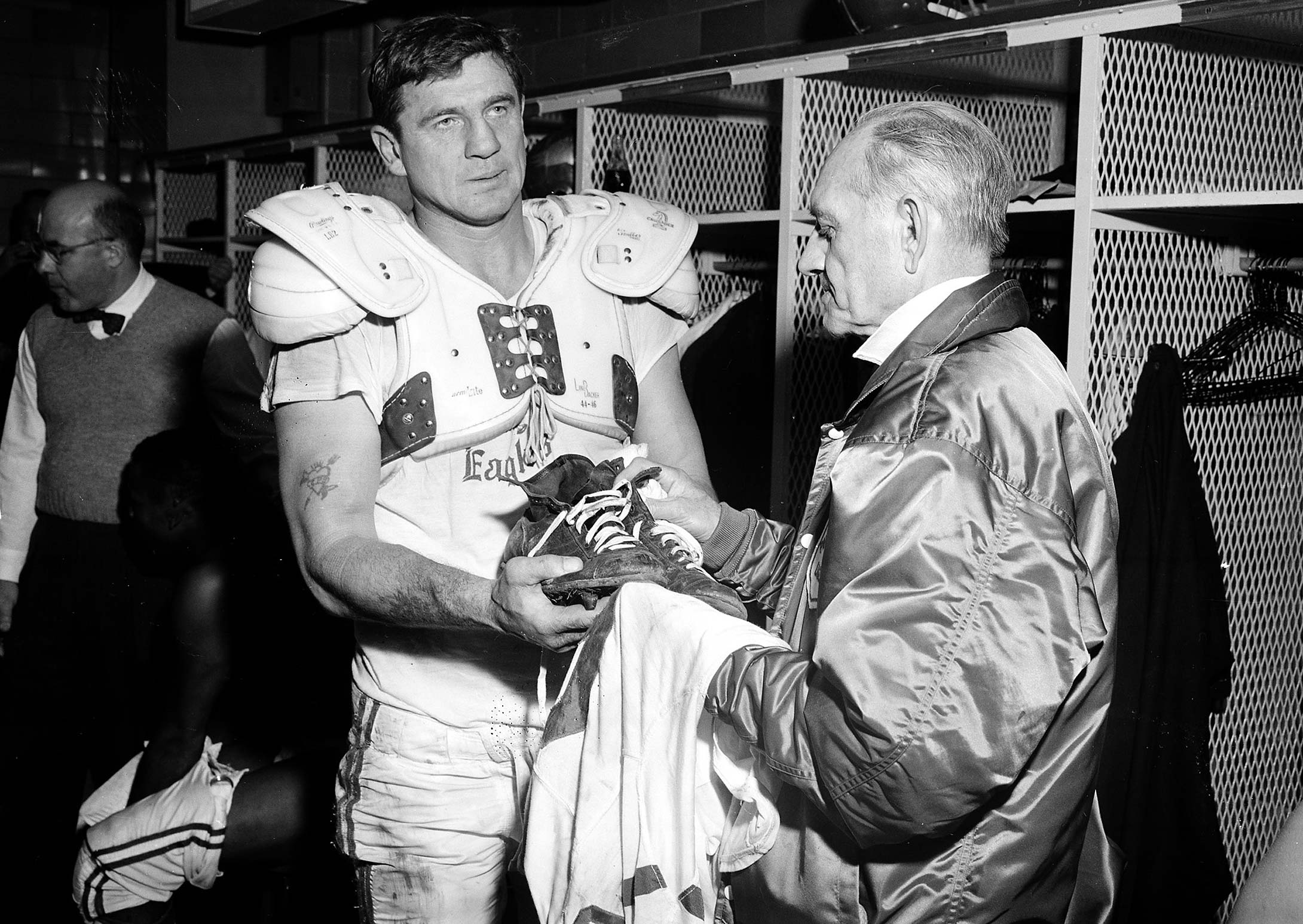 Chuck Bednarik hands his jersey and shoes to equipment manager Freddie Schubach after his last game so that they can be donated to the Hall of Fame.