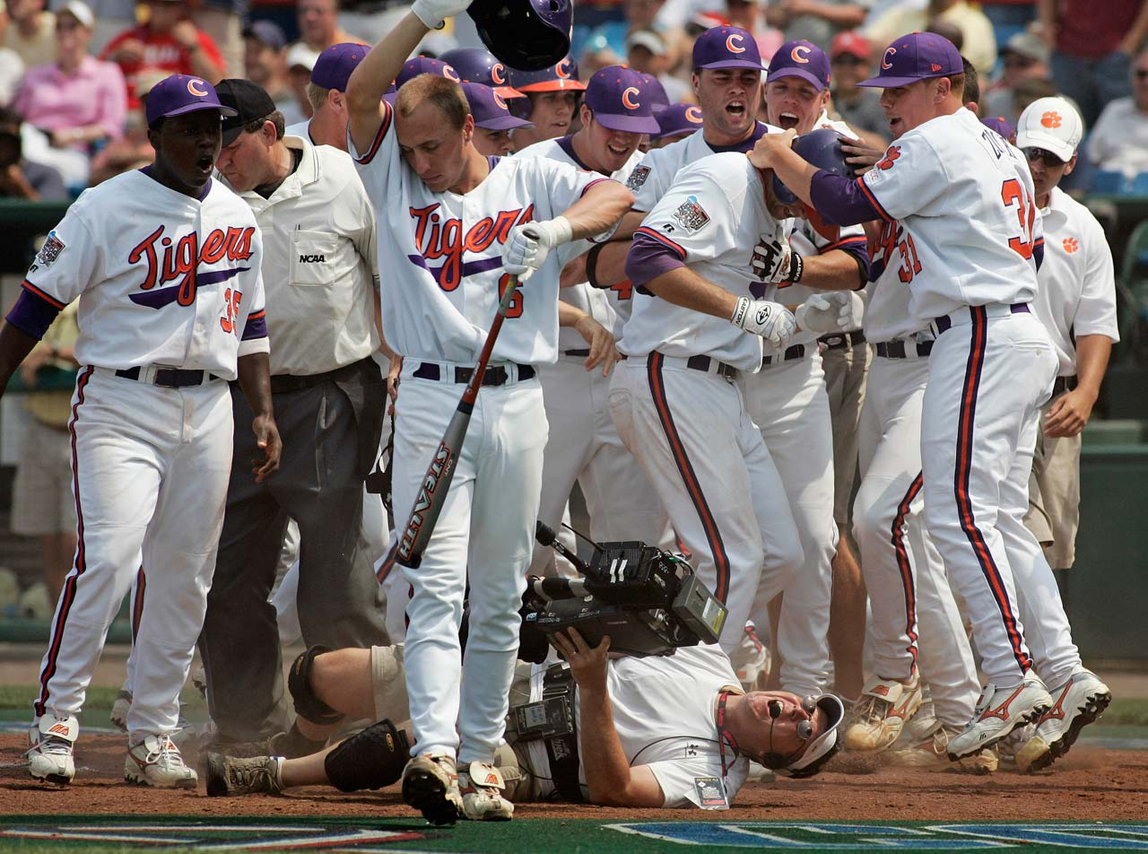 ESPN cameraman Mike Weir is knocked over as Clemson players celebrate a three-run home run by Andy D'Alessio in the eighth inning of the opening game of the 2006 NCAA baseball College World Series in Omaha, Neb.