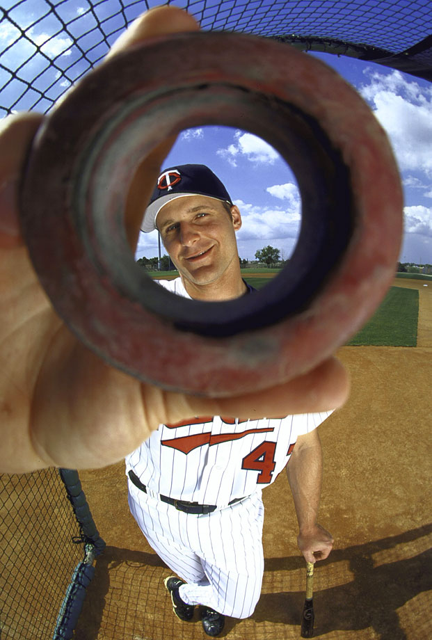 Minnesota Twins third baseman Corey Koskie looks through a weighted bat doughnut during spring training on March 19, 2000 in Fort Myers, Fla.