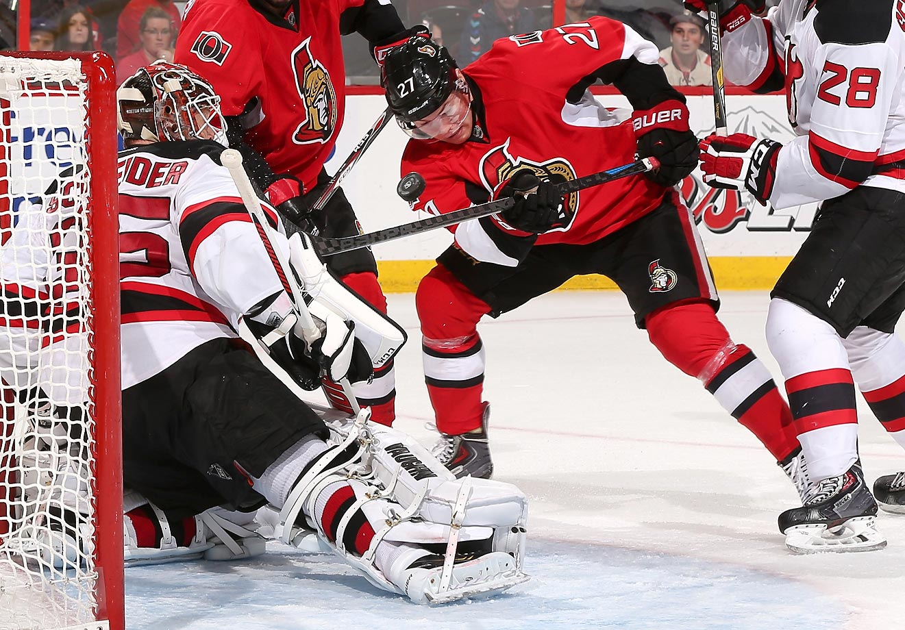 Curtis Lazar of the Senators swings at a loose puck against Cory Schneider of the Devils.